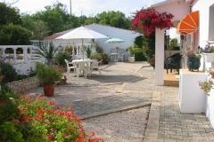 Die Gartenterrasse mit Tisch, Stühlen und Sonnenschirm.
