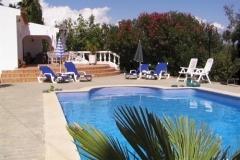 Ein Bild von der Pool mit Sonnenschirm und Liegestühlen.